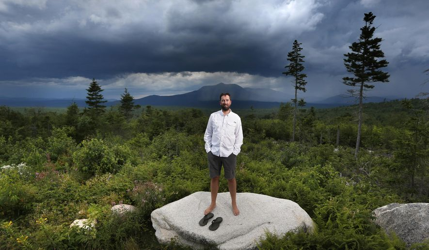 In this Tuesday, Aug. 4, 2015, photo, Lucas St. Clair poses on land proposed for a national park in Penobscot County, Maine. Mount Katahdin, the state's highest peak, can be seen in the background as a rainstorm passes through Baxter State Park. St. Clair is managing a non-profit foundation set up to promote the creation of a park on about 70,000 acres owned by his mother, Burt's Bees founder Roxanne Quimby. (AP Photo/Robert F. Bukaty)