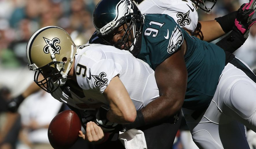 New Orleans Saints' Drew Brees, left, fumbles the ball after a hit from Philadelphia Eagles' Fletcher Cox during the second half of an NFL football game, Sunday, Oct. 11, 2015, in Philadelphia. (AP Photo/Michael Perez)