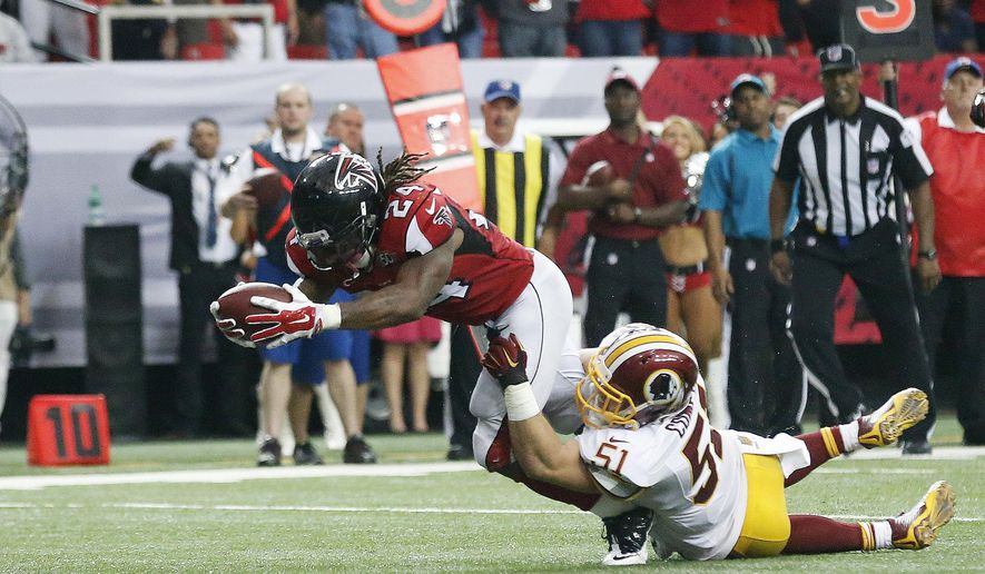 Atlanta Falcons running back Devonta Freeman (24) reaches for the goal line as Washington Redskins inside linebacker Will Compton (51) during the second half of an NFL football game, Sunday, Oct. 11, 2015, in Atlanta. The play was ruled a touchdown then reversed. (AP Photo/Brynn Anderson)