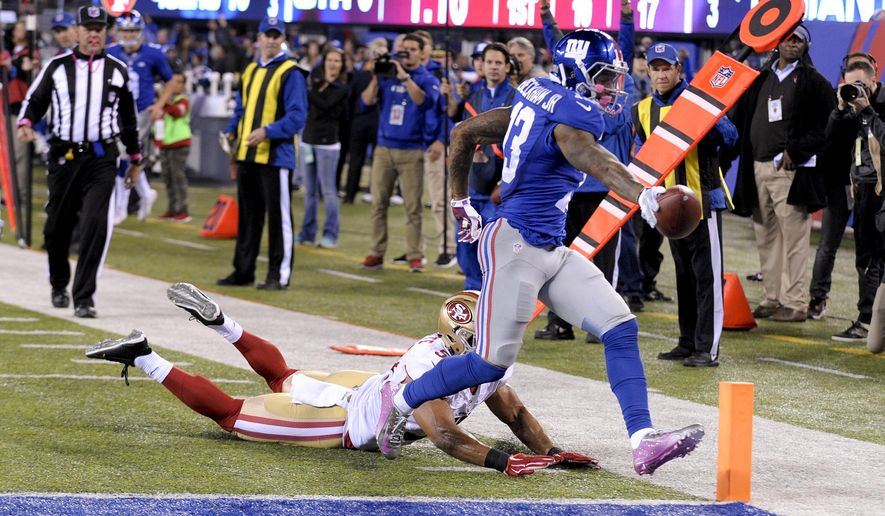 New York Giants wide receiver Odell Beckham (13) crosses the goal line for a touchdown as San Francisco 49ers inside linebacker Michael Wilhoite (57) defends during the third quarter of an NFL football game, Sunday, Oct. 11, 2015, in East Rutherford, N.J. (AP Photo/Bill Kostroun)