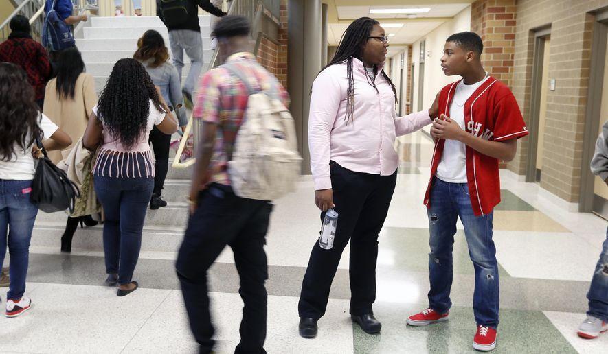 "ADVANCE FOR USE SUNDAY, OCT. 11 - In this photo taken Jan. 5, 2015, Ayanna Jones, head of the English department at Huguenot High School, in Richmond, Va., helps freshman Michael Roland find a class on the first day of school in the new Huguenot High School. Hailed at its opening in January by Richmond Mayor Dwight C. Jones as ""the Taj Mahal of high schools in the state of Virginia,"" officials say Huguenot High School has experienced some ""hiccups"" since students returned last month.  (Alexa Welch Edlund(/Richmond Times-Dispatch via AP)"
