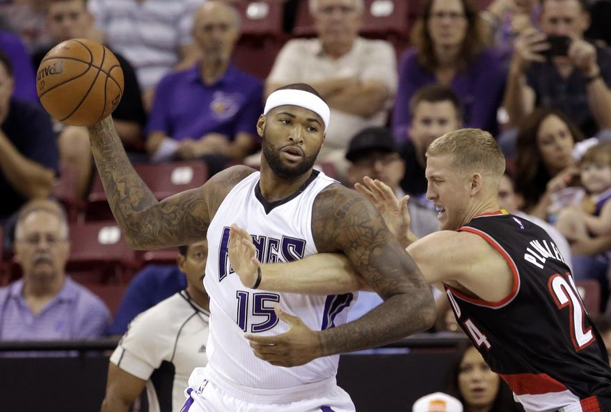 Sacramento Kings center DeMarcus Cousins, left, keeps the ball out of the reach of Portland Trail Blazers center Mason Plumlee during the first quarter of an NBA basketball game in Sacramento, Calif., Saturday, Oct. 10, 2015. (AP Photo/Rich Pedroncelli)