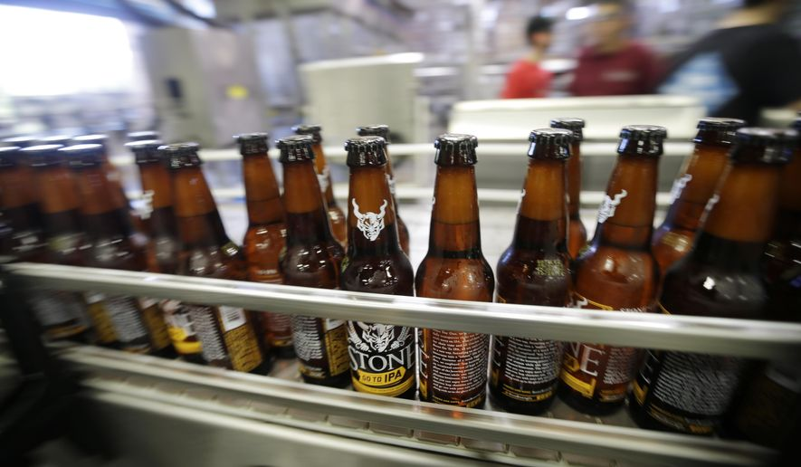 Bottles of beer move along during bottling at Stone Brewing Co., on Wednesday, Sept. 30, 2015, in Escondido, Calif. In an effort to reduce water use, the brewery is spending $1 million on expanding its $8 million wastewater treatment system installed in 2008, and aims to use only three gallons of water for every gallon of beer it produces. (AP Photo/Gregory Bull)