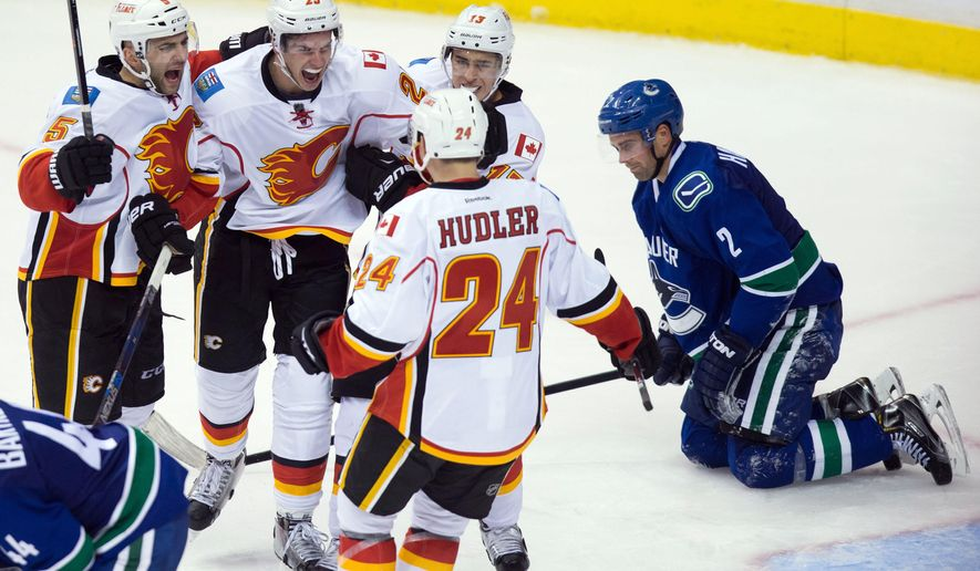 Calgary Flames' Mark Giordano (5), Sean Monahan (23), Johnny Gaudreau (13) and Jiri Hudler (24), of the Czech Republic, celebrate Monahan's goal as Vancouver Canucks' Dan Hamhuis, right, kneels on the ice during the third period of an NHL hockey game in Vancouver, British Columbia, Saturday, Oct. 10, 2015. (Darryl Dyck/The Canadian Press via AP) MANDATORY CREDIT