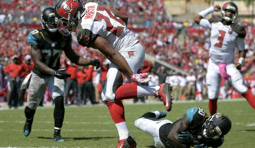 Tampa Bay Buccaneers running back Doug Martin (22) runs into the end zone after getting past Jacksonville Jaguars strong safety Johnathan Cyprien (37) and outside linebacker Telvin Smith (50) on a 1-yard touchdown run during the second quarter of an NFL football game Sunday, Oct. 11, 2015, in Tampa, Fla. (AP Photo/Phelan M. Ebenhack)