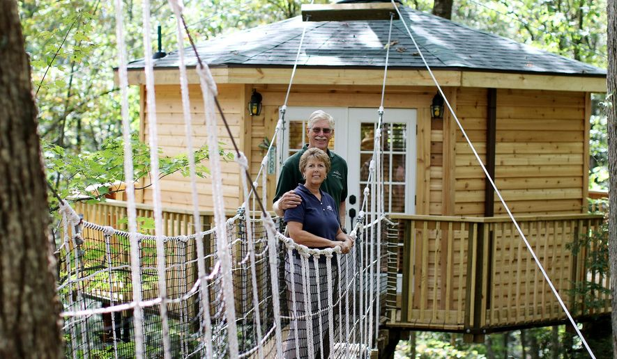 "ADVANCE FOR MONDAY OCT. 12 - In this Oct. 7, 2015 photo, Jennifer and Paul Breuer, owners of Country Roads Cabins pose in front of their newest cabin ""Holly Tree Cabin""  in Hico, W.Va. Country Road Cabins Rentals in Hico is offering a chance to enjoy a bird's-eye view in a new deluxe treehouse. (Chris Jackson/The Register-Herald via AP) MANDATORY CREDIT"