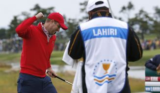 United States' Chris Kirk, left, celebrates after sinking a putt on the 18th green to defeat International team player Anirban Lahiri of India 1up in their singles match at the Presidents Cup golf tournament at the Jack Nicklaus Golf Club Korea, in Incheon, South Korea, Sunday, Oct. 11, 2015.(AP Photo/Lee Jin-man)