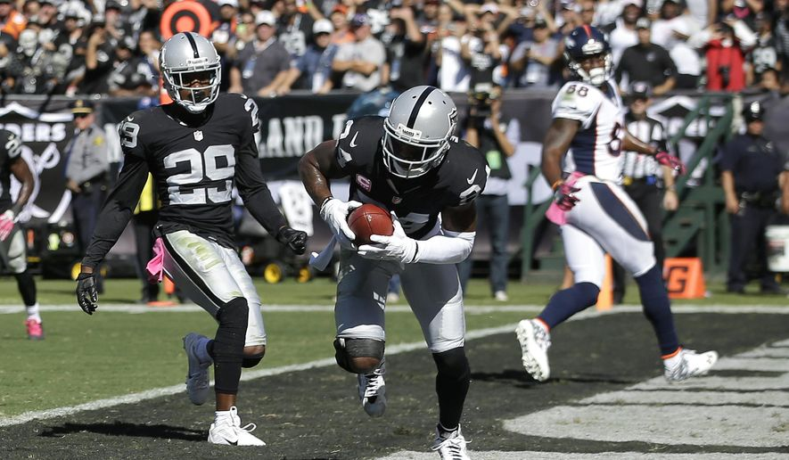 Oakland Raiders cornerback Charles Woodson, center, intercepts a pass by Denver Broncos quarterback Peyton Manning in the end zone during the first half of an NFL football game in Oakland, Calif., Sunday, Oct. 11, 2015. (AP Photo/Marcio Jose Sanchez)