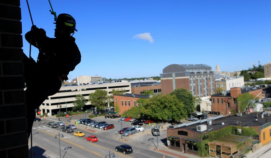 ADVANCE FOR USE SUNDAY, OCT. 11 - In this photo taken Friday, Oct. 2, 2015, Iowa City firefighter Jason Jordan rappels down the Court Street parking ramp during a high-rise emergency training in Iowa City, Iowa. The department trains roughly once a month at various locations around the area for different emergency situations regarding high-rise buildings. (David Scrivner/Iowa City Press-Citizen via AP)  NO SALES; MANDATORY CREDIT