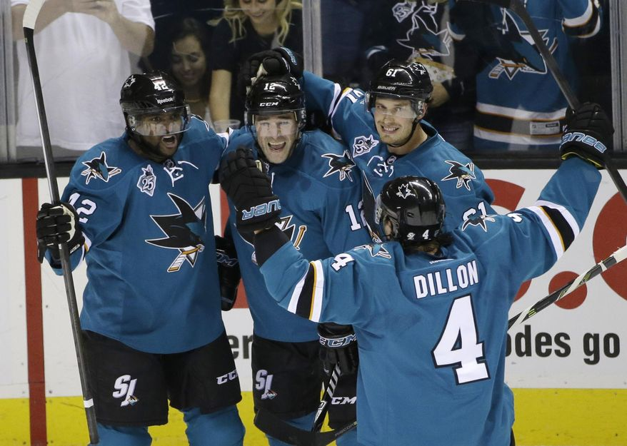 San Jose Sharks' Patrick Marleau (12) celebrates his goal with teammates Joel Ward (42), Justin Braun (61) and Brenden Dillon (4) during the second period of an NHL hockey game against the Anaheim Ducks Saturday, Oct. 10, 2015, in San Jose, Calif. (AP Photo/Marcio Jose Sanchez)