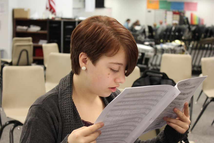 ADVANCE FOR THE WEEKEND OF OCT. 10-11 AND THEREAFTER. - In a Sept. 24, 2015 photo, Kayla Neeley reads sheet music during choir at Humphrey High School. Kayla was born with primary congenital glaucoma, which affects her vision. To read she has to hold the subject just inches from her face. It has not held her back; the 17-year-old senior is a semifinalist for the National Merit Scholarship. (Patrick Murphy/The Norfolk Daily News via AP)  MANDATORY CREDIT