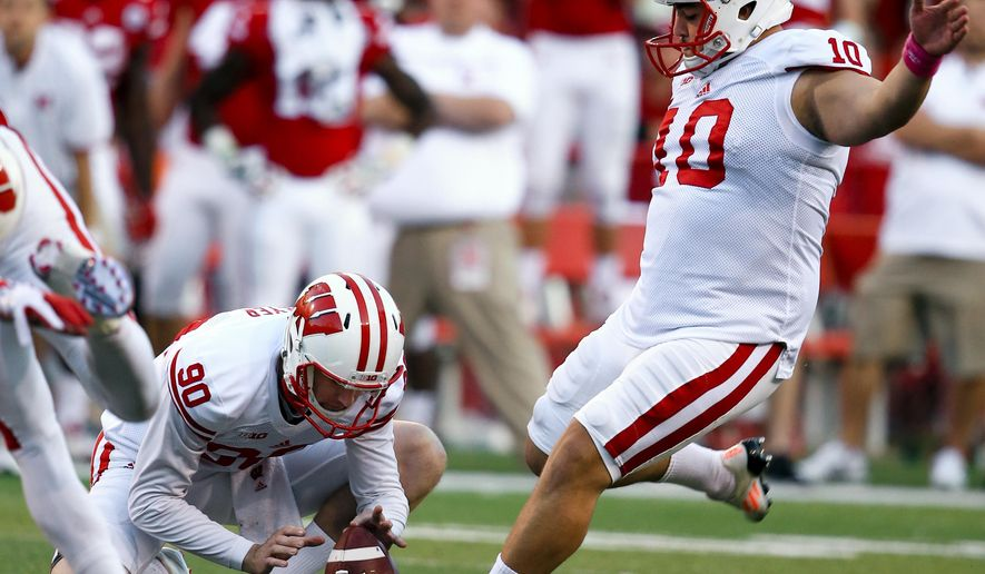 Wisconsin kicker Rafael Gaglianone (10) kicks the go-ahead and eventual game-winning field goal with Drew Meyer (90) holding, during the second half of an NCAA college football game against Nebraska in Lincoln, Neb., Saturday, Oct. 10, 2015. Wisconsin won 23-21. (AP Photo/Nati Harnik)