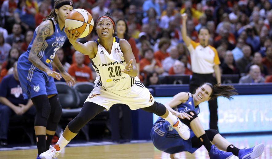Indiana Fever's Briann January, center, heads to the basket as Minnesota Lynx's Seimone Augustus, left, and Anna Cruz, right, watch in the first half of Game 4 of the WNBA Finals basketball series, in Indianapolis, Sunday, Oct. 11, 2015.  (AP Photo/Michael Conroy)