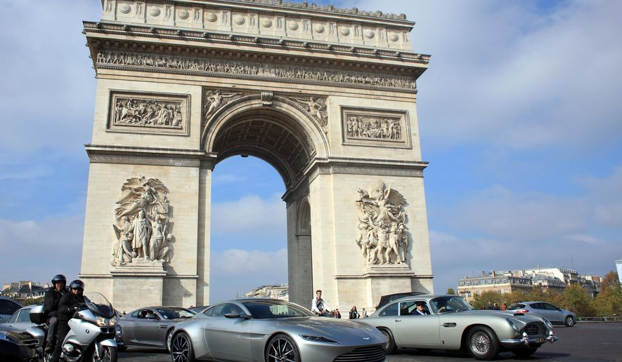 """An Aston Marton DB10, center, and DB5 on display, near the Arc of Triomphe, in Paris, Sunday, Oct. 11, 2015. Q branch is paying a visit to Paris with the arrival of nearly 20 cars featured in James Bond films over the years. From the Sunbeam Alpine in the 1962 """"Dr. No"""" to this year's Aston Martin, the cars paraded down the Champs Elysees on Sunday after arraying in front of the Arc de Triomphe. (AP Photo/Thibault Camus)"""