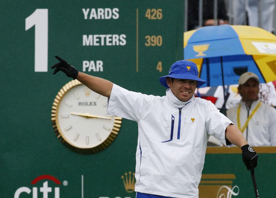 International team player Louis Oosthuizen of South Africa gestures after hitting his ball on the first tee during his singles match against United States' Patrick Reed at the Presidents Cup golf tournament at the Jack Nicklaus Golf Club Korea, in Incheon, South Korea, Sunday, Oct. 11, 2015.(AP Photo/Lee Jin-man)