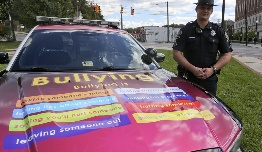 ADVANCE FOR USE SUNDAY, OCT. 11 - In this photo taken Wednesday, Oct. 7, 2015, school resource officer Allan Klein, of the Christiansburg Police Department, poses with department's new anti-bullying themed police car on the front lawn of Town Hall in Christiansburg Va. (Matt Gentry/The Roanoke Times via AP) LOCAL TELEVISION OUT; SALEM TIMES REGISTER OUT; FINCASTLE HERALD OUT;  CHRISTIANBURG NEWS MESSENGER OUT; RADFORD NEWS JOURNAL OUT; ROANOKE STAR SENTINEL OUT; MANDATORY CREDIT