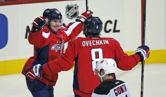 Washington Capitals center Marcus Johansson (90), from Sweden, celebrates his goal with left wing Alex Ovechkin (8), from Russia, with New Jersey Devils right wing Stephen Gionta (11) nearby during the third period of an NHL hockey game, Saturday, Oct. 10, 2015, in Washington. (AP Photo/Alex Brandon)