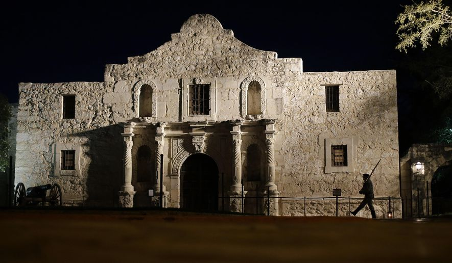 FILE - In this March 6, 2013, file photo, John Potter, a member of the San Antonio Living History Association, patrols the Alamo in San Antonio, during a pre-dawn memorial ceremony to remember the 1836 Battle of the Alamo and those who fell on both sides. The former 18th century Spanish mission is poised to undergo one of the most significant transformations in its history as the state moves to purchase nearby commercial buildings and launch a planning review that could bring dramatic changes. (AP Photo/Eric Gay, File)