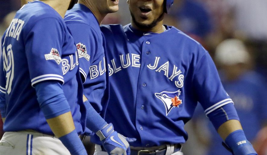 After hitting a three-run home run against the Texas Rangers, Toronto Blue Jays shortstop Troy Tulowitzki, center celebrates with right fielder Jose Bautista (19), and designated hitter Edwin Encarnacion (10), right, during the sixth inning in Game 3 of baseball's American League Division Series Sunday, Oct. 11, 2015, in Arlington, Texas. (AP Photo/LM Otero)