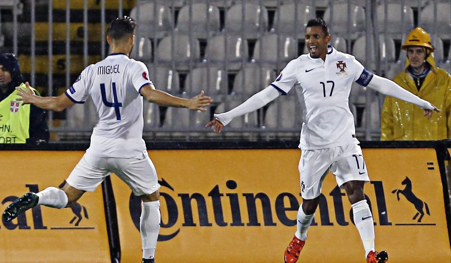 Portugal's Nani, right celebrates with teammate Miguel Veloso after scoring the first goal of his team during the Euro 2016 Group I qualifying match between Serbia and Portugal, at the Partizan stadium in Belgrade, Serbia, Sunday, Oct. 11, 2015.  (AP Photo/Darko Vojinovic)