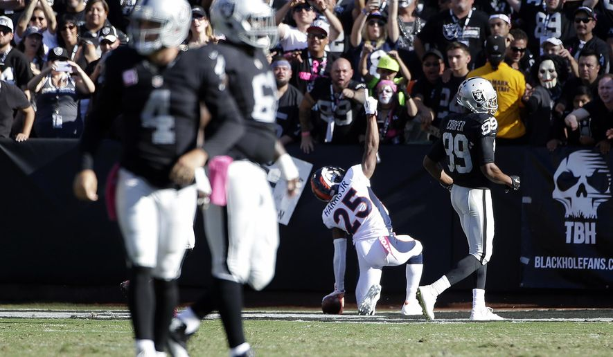Denver Broncos cornerback Chris Harris (25) celebrates after returning an interception from Oakland Raiders quarterback Derek Carr (4) for a 74-yard touchdown during the second half of an NFL football game in Oakland, Calif., Sunday, Oct. 11, 2015. (AP Photo/Marcio Jose Sanchez)