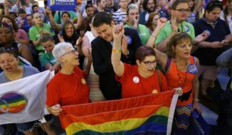 In this June 26, 2015, file photo, same-sex marriage supporters cheer at the Statehouse in Indianapolis after the Supreme Court declared that same-sex couples have a right to marry anywhere in the United States. (AP Photo/Michael Conroy, File)