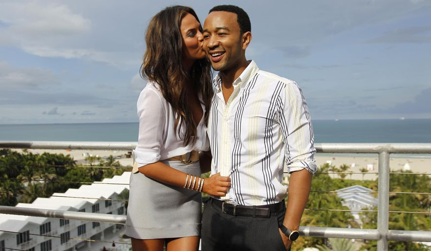 FILE - In this July 18, 2011 file photo, model Chrissy Teigen, left, and singer John Legend pose for photos after the Dineila Brazil swim suit show during the Mercedes-Benz Fashion Week in Miami Beach, Fla. Teigen and Legend announced on their Instagram accounts, Monday, Oct. 12, that they are expecting their first child. (AP Photo/J Pat Carter, File)