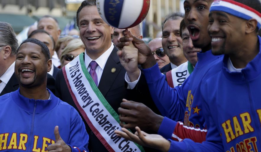 New York Governor Andrew Cuomo, second from left, poses for a picture with members of the Harlem Globetrotters before marching in the Columbus Day Parade in New York, Monday, Oct. 12, 2015. Approximately 35,000 marchers participated in the annual celebration of Italian-American culture. (AP Photo/Seth Wenig)