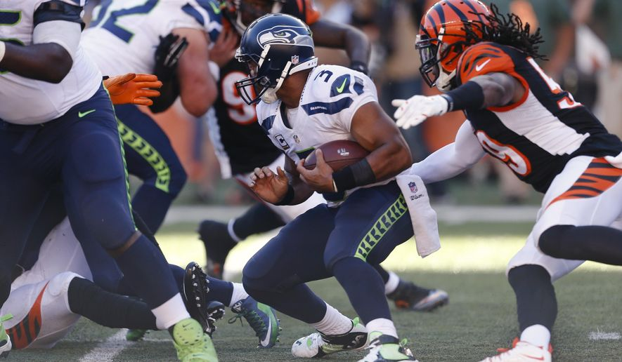 Seattle Seahawks quarterback Russell Wilson (3) is sacked by Cincinnati Bengals defensive end Wallace Gilberry, right, in overtime of an NFL football game, Sunday, Oct. 11, 2015, in Cincinnati. (AP Photo/Gary Landers)