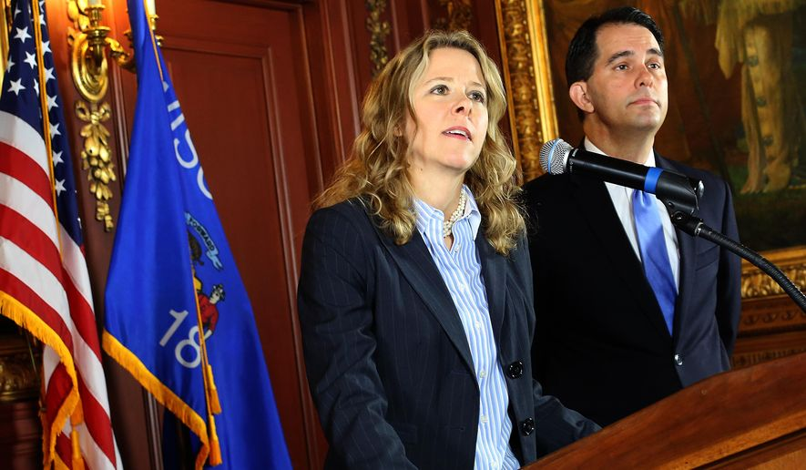 Judge Rebecca Bradley makes remarks to members of the media after it was announced that she was being appointed to the Wisconsin Supreme Court by Governor Scott Walker, rigth,  at the State Capitol in Madison, Wis. Friday, Oct. 9, 2015. Bradley, 44, who had previously announced her candidacy for the seat of retiring Justice Patrick Crooks, was tabbed by Walker to fill the unexpected vacancy on the court after Crooks died in September.  (John Hart/Wisconsin State Journal via AP) MANDATORY CREDIT