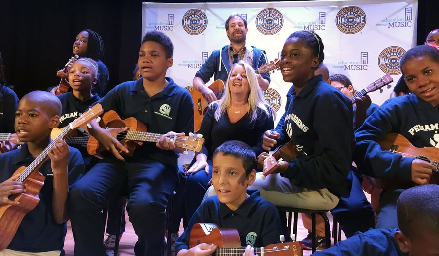 In this Oct. 5, 2015 photo, Liz Rose, center, a Grammy-award winning country music songwriter from Nashville, rehearses a song with students at Pelham Gardens Middle School in the Bronx borough of New York. Rose is working with the students through a program funded by the Country Music Association Foundation which provides a curriculum for teachers to develop language skills through the art of songwriting. (AP Photo/William Mathis)
