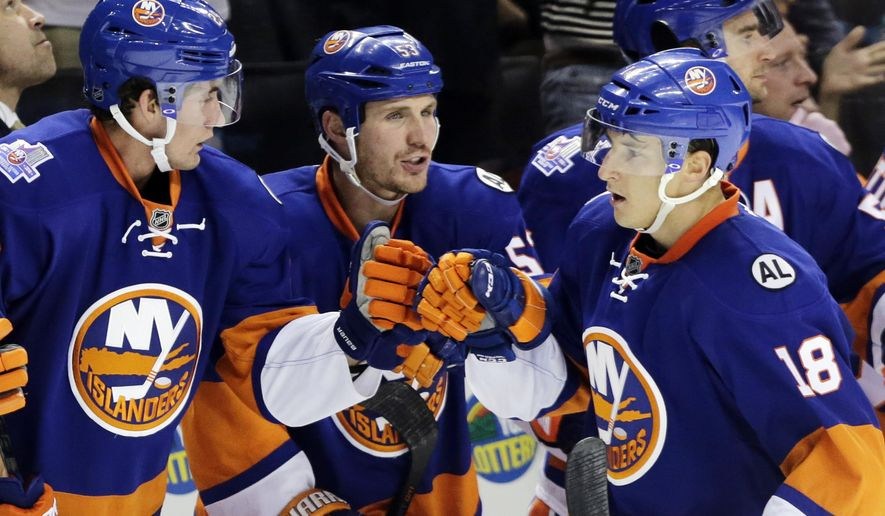 CORRECTS TO OCT. 12 NOT 11 - New York Islanders center Ryan Strome (18) is congratulated by teammates Brock Nelson, left, and Casey Cizikas (53), center, after scoring a  power-play goal in the first period of an NHL hockey game against the Winnipeg Jets, Monday, Oct. 12, 2015, in New York. (AP Photo/Mark Lennihan)