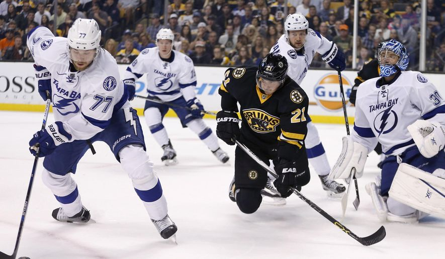 Tampa Bay Lightning's Victor Hedman (77) moves to clear the puck in front of Boston Bruins' Loui Eriksson (21) during the second period of an NHL hockey game in Boston, Monday, Oct. 12, 2015. (AP Photo/Michael Dwyer)