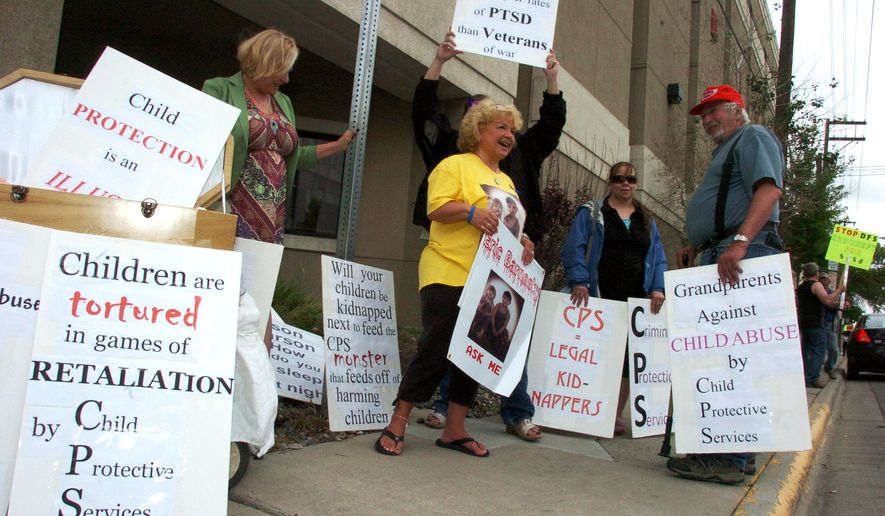 FILE - In this June 5, 2015 file photo, Patsy Fercho,  center, protests outside the Montana Department of Public Health and Human Services office in Billings, Mont., with others who are upset about how the Division of Child and Family Services handles placement of children in abuse and neglect cases. Fercho is hiding out from the law, caught in a legal limbo between state and tribal courts as she tries to gain custody of her grandsons. (AP Photo/Matthew Brown, File)