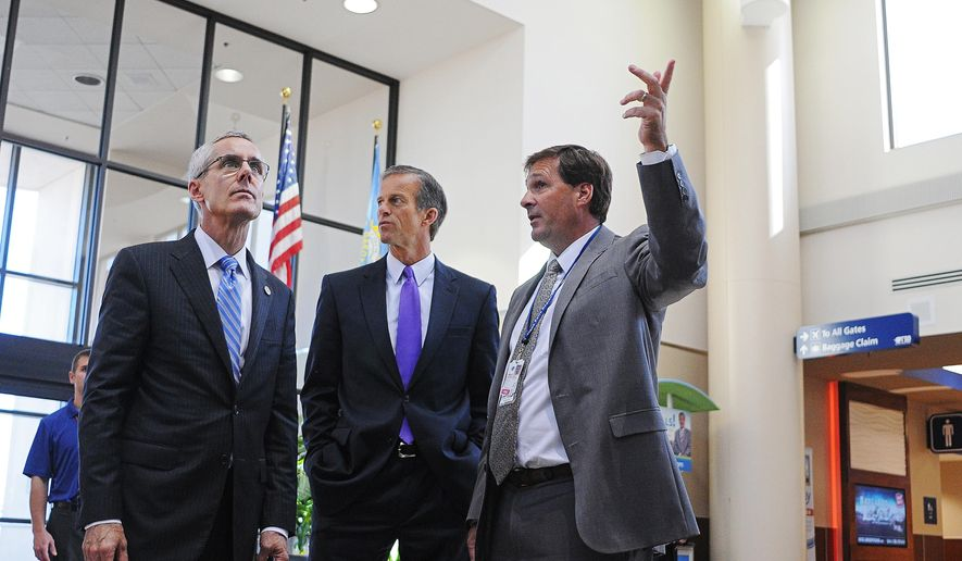 Admiral Peter Neffenger, left, head of the Transportation Security Administration, gets a tour of the Sioux Falls Regional Airport from Dan Letellier, right, executive director, as U.S. Sen. John Thune looks on Monday, Oct. 12, 2015, in Sioux Falls, S.D. (Joe Ahlquist/Argus Leader via AP)