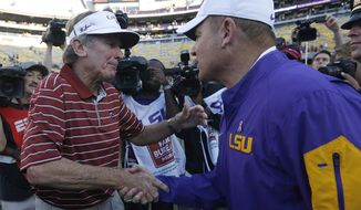 FILE - In this Saturday, Oct. 10, 2015, file photo, South Carolina head coach Steve Spurrier, left, and LSU head coach Les Miles shake hands after an NCAA college football game in Baton Rouge, La. LSU won 45-24. Spurrier is retiring in the middle of his 11th season with South Carolina, sources confirmed. (AP Photo/Jonathan Bachman, File)