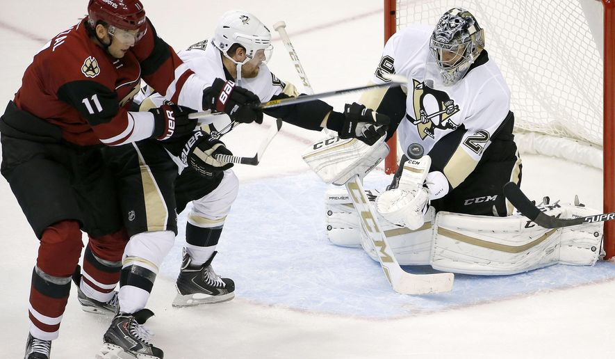 Arizona Coyotes' Martin Hanzal (11), of the Czech Republic, gets his shot deflected by Pittsburgh Penguins' Marc-Andre Fleury, right, as Penguins' Phil Kessel, center, defends during the third period of an NHL hockey game Saturday, Oct. 10, 2015, in Glendale, Ariz.  The Coyotes defeated the Penguins 2-1. (AP Photo/Ross D. Franklin)