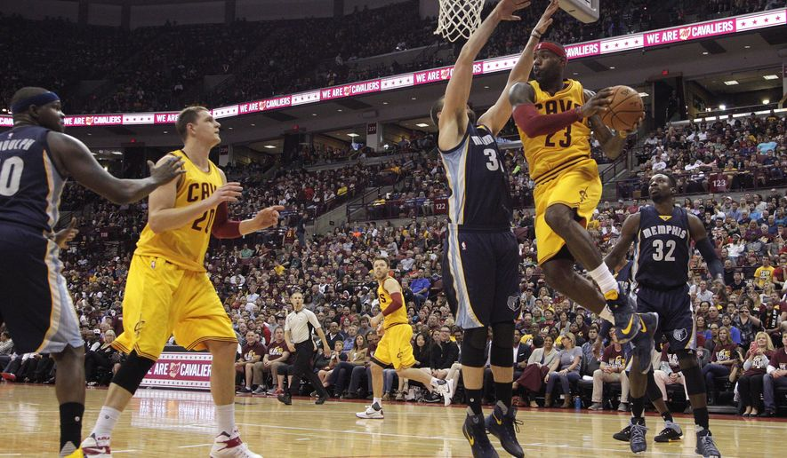 Cleveland Cavaliers' LeBron James (23) drives to the basket between Memphis Grizzlies' Jeff Green, right, and Marc Gasol, of Spain, during the second quarter of an NBA preseason basketball game Monday, Oct. 12, 2015, in Columbus, Ohio. (AP Photo/Jay LaPrete)