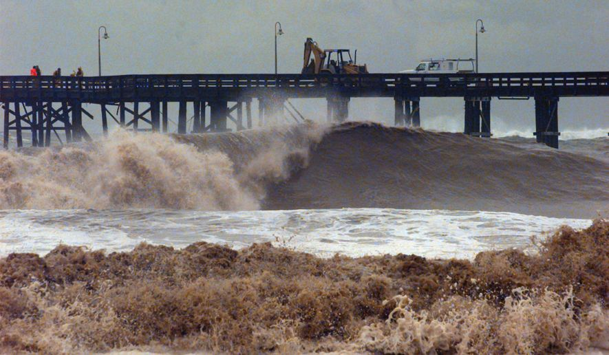 FILE - In this Feb. 2, 1998 file photo, work crews attempt to repair a damaged pier caused by waves that reached 15 feet from the massive El Nino-driven storm in Ventura, Calif. Evidence is mounting that the El Nino ocean-warming phenomenon in the Pacific will spawn a rainy winter in California, potentially easing the state's punishing drought but also bringing the risk of chaotic storms like those that battered the region in the late 1990s. (AP Photo/Nick Ut,File)
