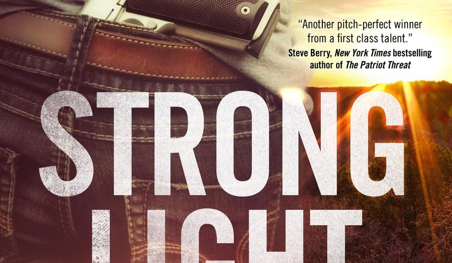 "This photo provided by Forge Books shows the cover of the book, ""Strong Light of Day,"" by author Jon Land. (Forge Books via AP)"