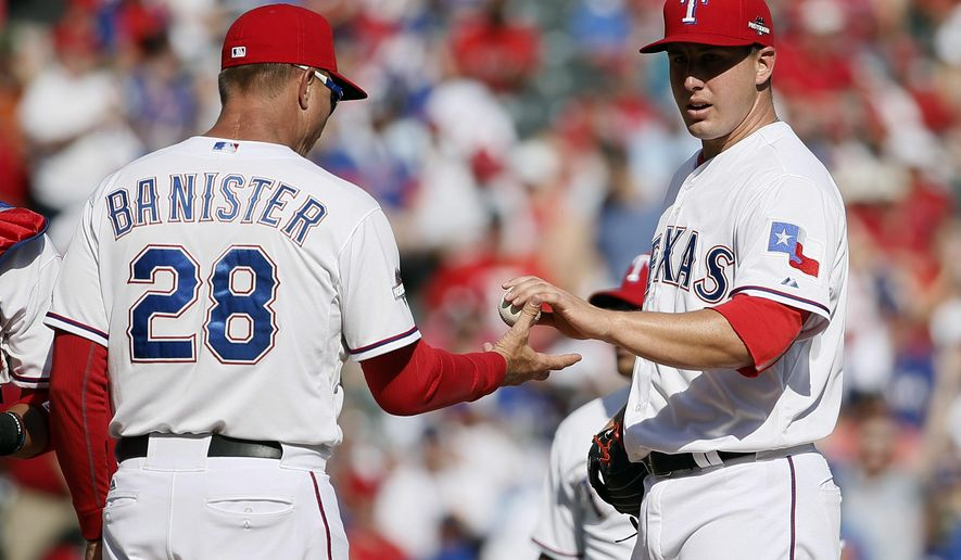 Texas Rangers manager Jeff Banister (28) takes starting pitcher Derek Holland (45) out of the game against the Toronto Blue Jays during the third inning in Game 4 of baseball's American League Division Series Monday, Oct. 12, 2015, in Arlington, Texas. (AP Photo/Tony Gutierrez)
