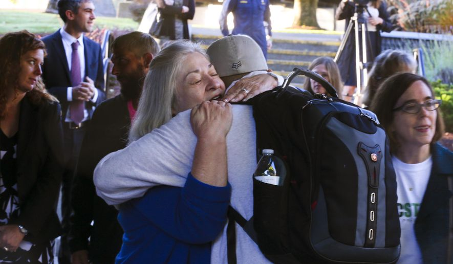 ADDS NAME OF WOMAN HUGGING - Umpqua Community College interim President Rita Cavin hugs an unidentified person on campus as the school reopens, Monday, Oct. 12, 2015, after being closed since the multiple fatality shooting on Oct. 1, in Roseburg, Ore. (Beth Nakamura/The Oregonian via AP, Pool)