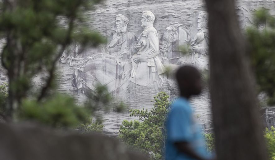 """FILE - In this Tuesday, June 23, 2015, file photo, a youngster plays on a rock in front of the carving on Stone Mountain, in Stone Mountain, Ga. The carving depicts confederates Robert E. Lee, Jefferson Davis and Stonewall Jackson. Planning is underway to place a replica of the Liberty Bell atop Stone Mountain as a memorial to the Rev. Martin Luther King Jr. that recalls a famous line from his """"I Have a Dream"""" speech, officials say. (AP Photo/John Bazemore, File)"""