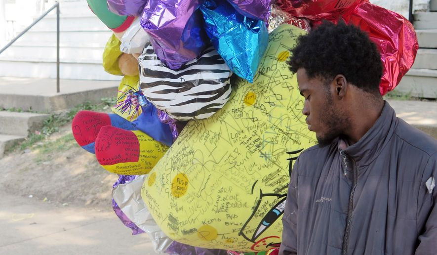 In this Aug. 27, 2015 photo, Jamel Russel, 17, looks at a memorial for his friend Breanna Eskridge, who was gunned down on her grandmother's front porch in Milwaukee. Community activists and city officials across the U.S. grapple with whether, or when, to remove tributes to victims of gun violence. In Milwaukee, victims' advocates are leading a push to establish publicly funded individual tributes to replace makeshift shrines. (AP Photo/Greg Moore)
