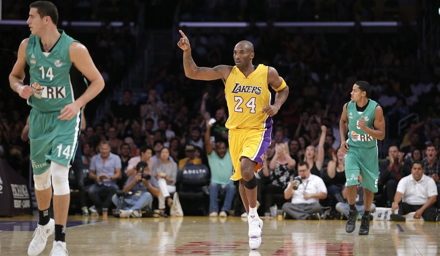 Los Angeles Lakers' Kobe Bryant, center, makes his way down the court after making a three-point basket during the first half of an NBA preseason basketball game against Maccabi Haifa, Sunday, Oct. 11, 2015, in Los Angeles. (AP Photo/Jae C. Hong)