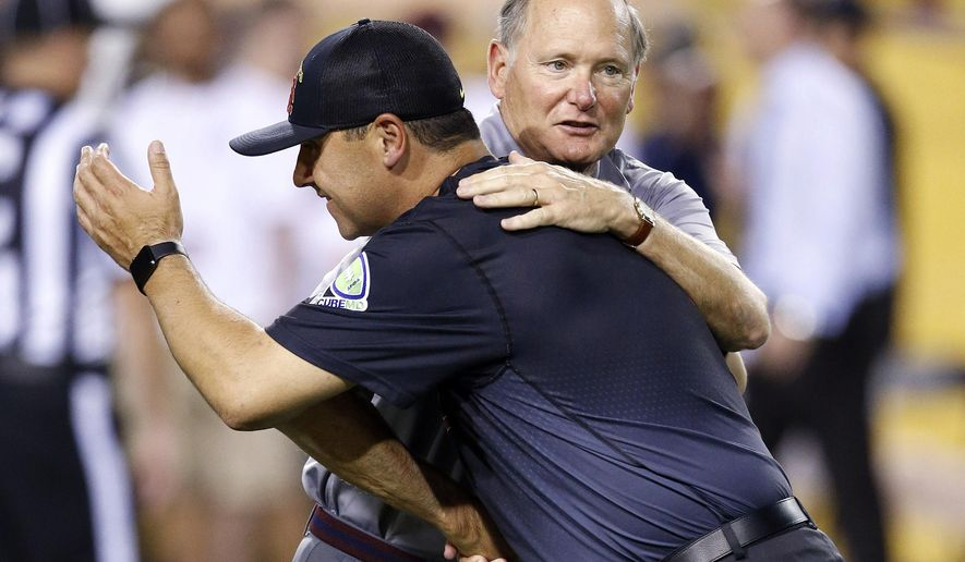 FILE - In this Sept. 26, 2015, file photo, Southern California coach Steve Sarkisian, front, hugs USC athletic director Pat Haden prior to the team's NCAA college football game against Arizona State in Tempe, Ariz. USC fired Sarkisian one day after the troubled coach was put on leave. Athletic director Pat Haden announced his decision Monday, Oct. 12, 2015, in a brief statement. (AP Photo/Ross D. Franklin, File)