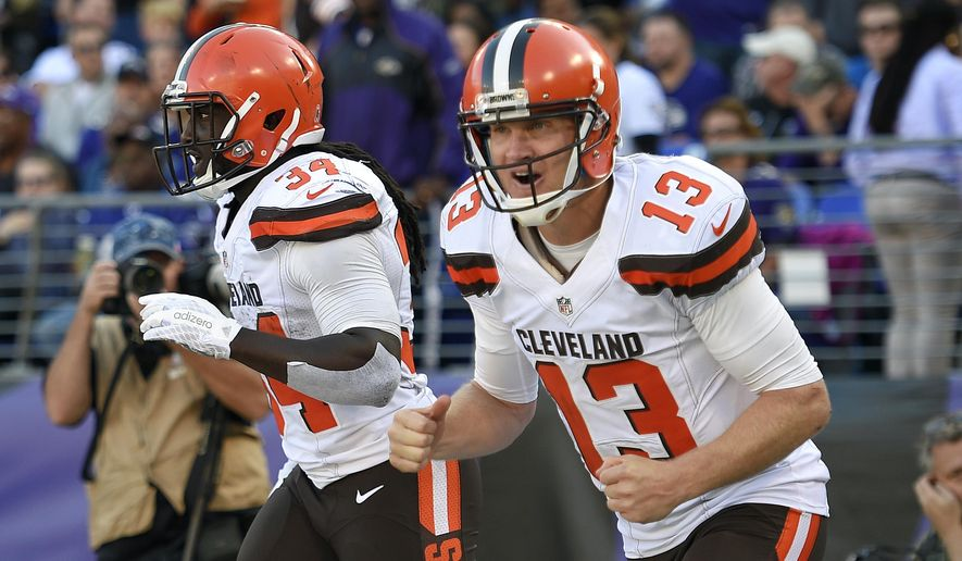 Cleveland Browns quarterback Josh McCown, right, and running back Isaiah Crowell celebrate McCown's touchdown pass to Crowell in the second half of an NFL football game against the Baltimore Ravens, Sunday, Oct. 11, 2015, in Baltimore. Cleveland won 33-30 in overtime. (AP Photo/Nick Wass)