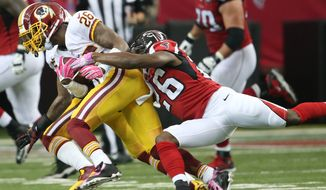 Washington Redskins cornerback Bashaud Breeland (26) is tackled after intercepting a Matt Ryan thrown ball as Atlanta Falcons running back Tevin Coleman (26) makes the tackle during the second half of an NFL football game, Sunday, Oct. 11, 2015, in Atlanta. (AP Photo/John Bazemore)
