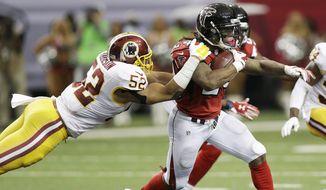 Atlanta Falcons running back Devonta Freeman (24) pulls Washington Redskins inside linebacker Keenan Robinson (52) during the second half of an NFL football game, Sunday, Oct. 11, 2015, in Atlanta. (AP Photo/Brynn Anderson)
