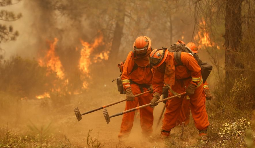 A California Department of Corrections and Rehabilitation inmate work crew builds a containment line ahead of flames from a fire near Sheep Ranch, Calif., in this Sept. 12, 2015, file photo. (AP Photo/Rich Pedroncelli, File)